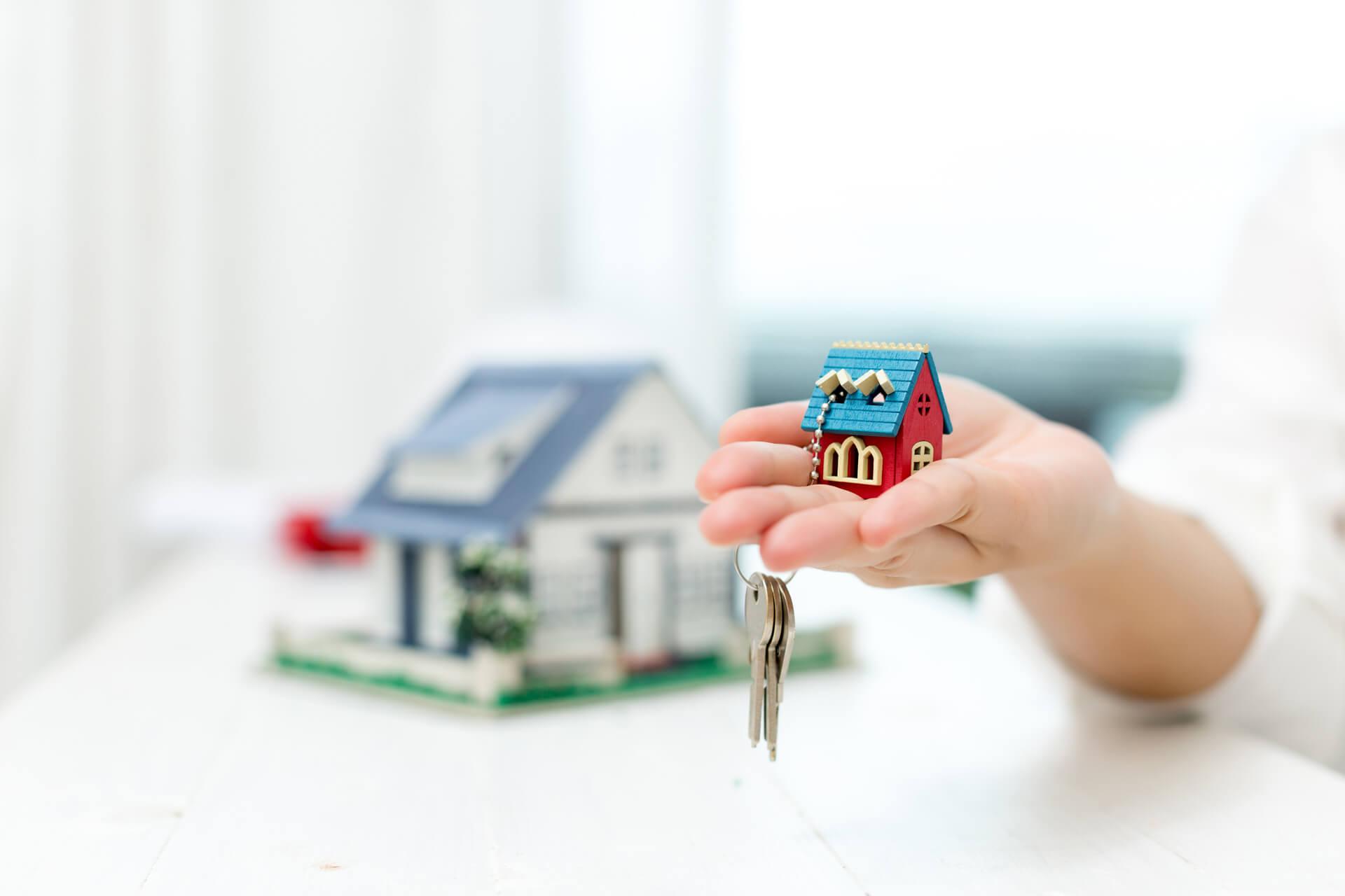 Agente de imóveis segurando modelo e chaves
